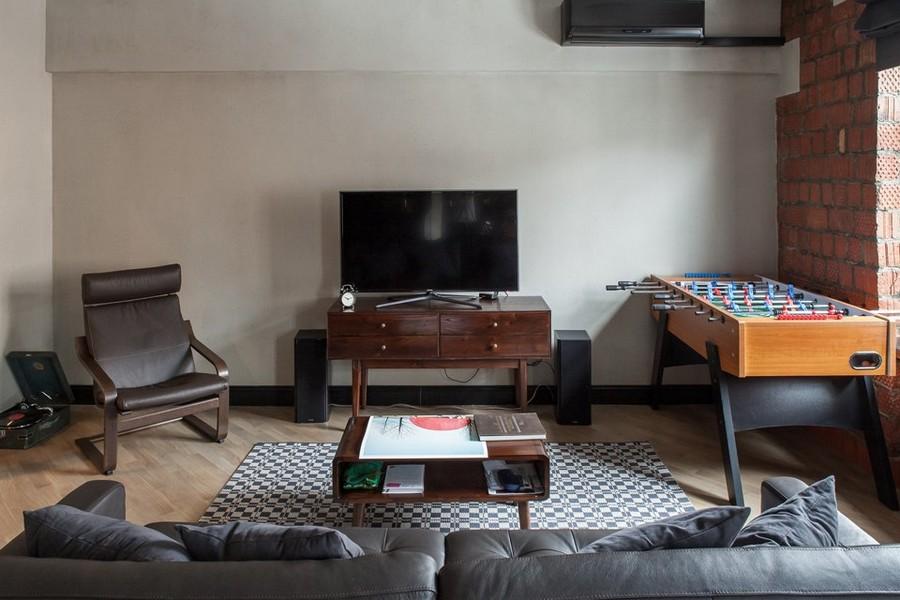 1-2-bachelor's-pad-interior-design-loft-style-brutal-lounge-living-room-TV-set-console-soccer-table-rocking-chair-black-sofa-light-laminate-floor-buidling-bricks-masonry-wall-brown