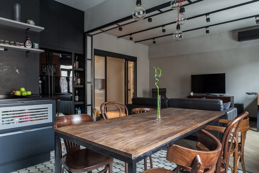 1-4-bachelor's-pad-interior-design-loft-style-brutal-open-concept-kitchen-set-dining-living-room-black-track-lights-bulbs-exposed-wires-chalkboard-wall-mismatched-wooden-chairs-table