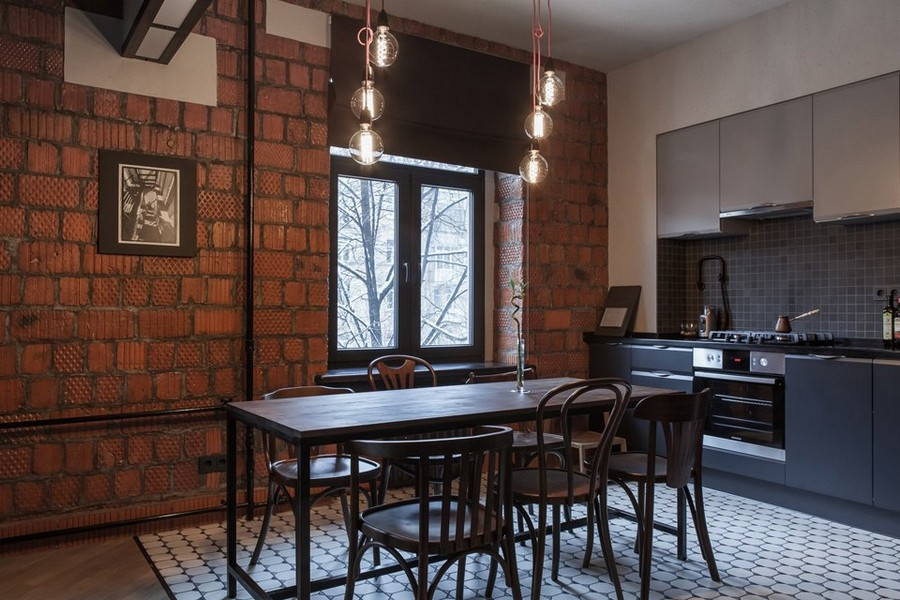 2-0-bachelor's-pad-interior-design-loft-style-brutal-dining-room-black-kitchen-set-building-bricks-rough-masonry-wall-bulbs-exposed-wires-mismatched-dining-chairs-table-floor-tiles