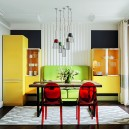 2-1-interior-in-mid-century-modern-style-pop-art-geometrical-motifs-1950s-bright-color-multicolor-kitchen-symmetrical-yellow-cupboards-refrigerator-free-standing-green-sofa-red-dining-chairs-table-rug-suspended-floating