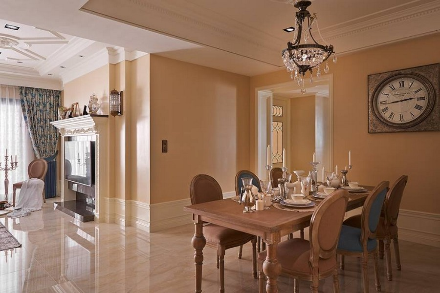 2-1-neo-classical-style-interior-neutral-beige-blue-Tuscan-colors-open-plan-concept-dining-living-room-wall-clock-wooden-table-mismatched-chairs-crystal-chandelier-wall-panels