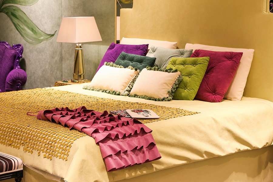 2-1-new-show-room-concept-store-in-Milan-Italy-2017-Alcantara-material-collection-in-interior-design-bedroom-pale-yellow-upholstered-bed-multicolor-ruffle-throw-pillows-decorative-green-fuchsia-purple-white