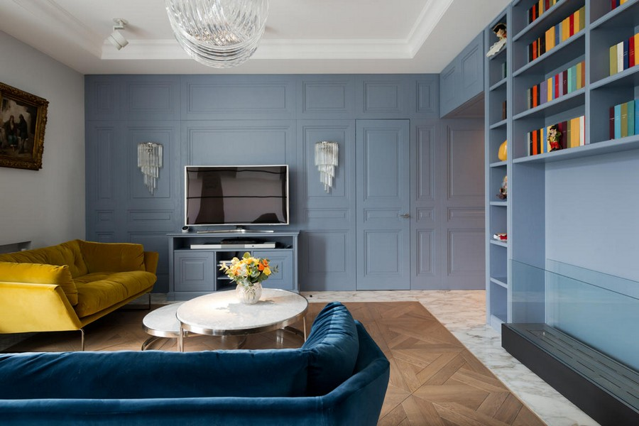 2-2-American-style-interior-wooden-wall-panelling-invisible-door-living-room-velvet-sofa-blue-green-bio-fireplace-TV-metal-coffee-tables-big-home-library-book-shelves-sconces-classical-picture
