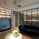 3-1-American-style-interior-wooden-panelling-glass-wall-between-kitchen-and-living-room-black-metal-frame-big-home-library-blue-velvet-sofa-bio-fireplace-coffee-table