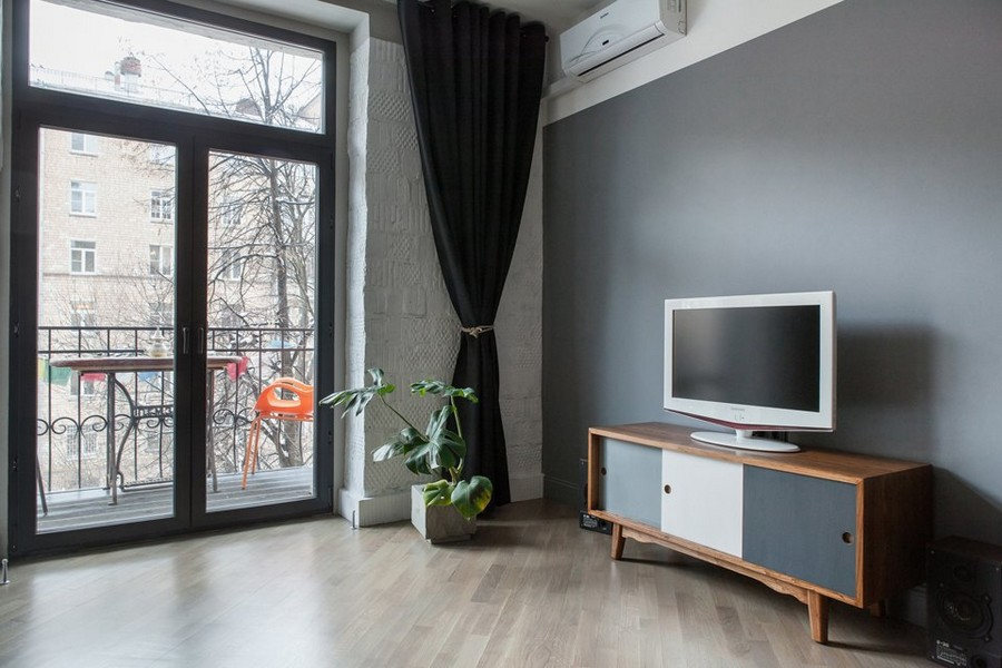 3-2-bachelor's-pad-interior-design-loft-style-brutal-lounge-with-balcony-exit-minimalism-gray-white-TV-set-stand-cabinet-air-conditioner-graphite-wall-black-curtains-light-laminate
