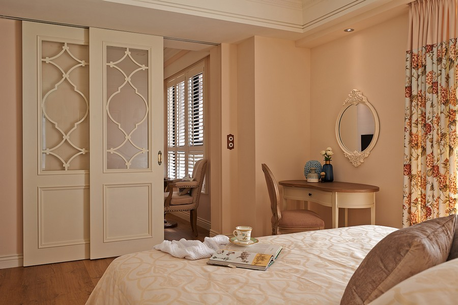 4-1-neo-classical-style-interior-neutral-beige-blue-Tuscan-colors-bedroom-bed-dressing-table-chair-carved-mirror-frame-sliding-white-door-with-glass-inserts-floral-curtains-flowers-tea-tray