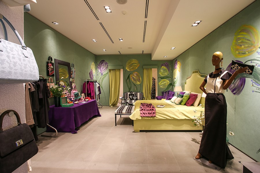 4-2-new-show-room-concept-store-in-Milan-Italy-2017-Alcantara-material-collection-in-interior-design-bedroom-pale-yellow-upholstered-bed-headboard-throw-pillows-purple-dressing-table-cloth-fabric-mannequin-bags-curtains