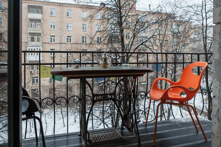 4-balcony-interior-design-old-vintage-remade-sewing-machine-framework-reused-as-coffee-table-forged-railing-mismatched-plastic-chairs-orange-and-brown-antique-tea-pot