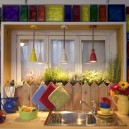 4-cozy-country-house-kitchen-wooden-in-Mediterranean-style-bright-multicolored-red-yellow-blue-glass-blocks-interior-window-herbs-indoor-planted-suspended-lamps-picket-fence-wooden-worktop-garlick-twigs-still-life