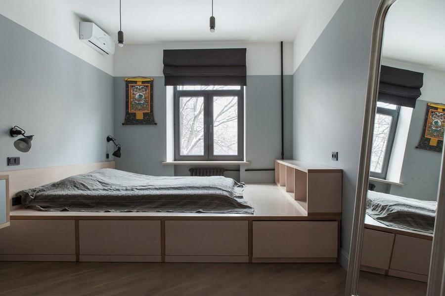 5-1-bachelor's-pad-interior-design-loft-style-brutal-bedroom-light-wooden-poidum-with-storage-drawers-mattress-book-shelves-big-full-length-mirror-gray-walls-black-roman-blinds
