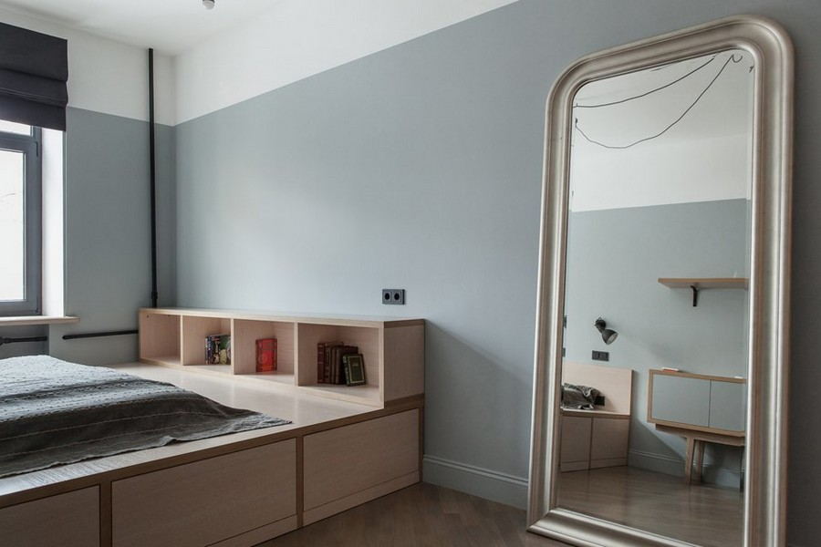 5-2-bachelor's-pad-interior-design-loft-style-brutal-bedroom-light-wooden-poidum-with-storage-drawers-mattress-book-shelves-big-full-length-mirror-gray-walls-black-roman-blinds