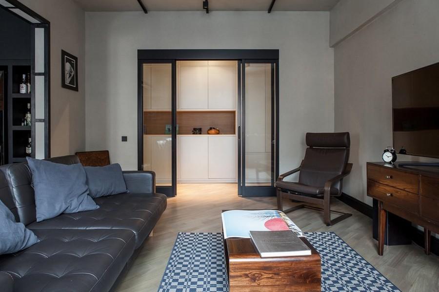 6-2-bachelor's-pad-interior-design-loft-style-brutal-living-room-lounge-sliding-glass-doors-brown-chair-black-leather-sofa-rug-TV-built-in-closet-corridor-exit