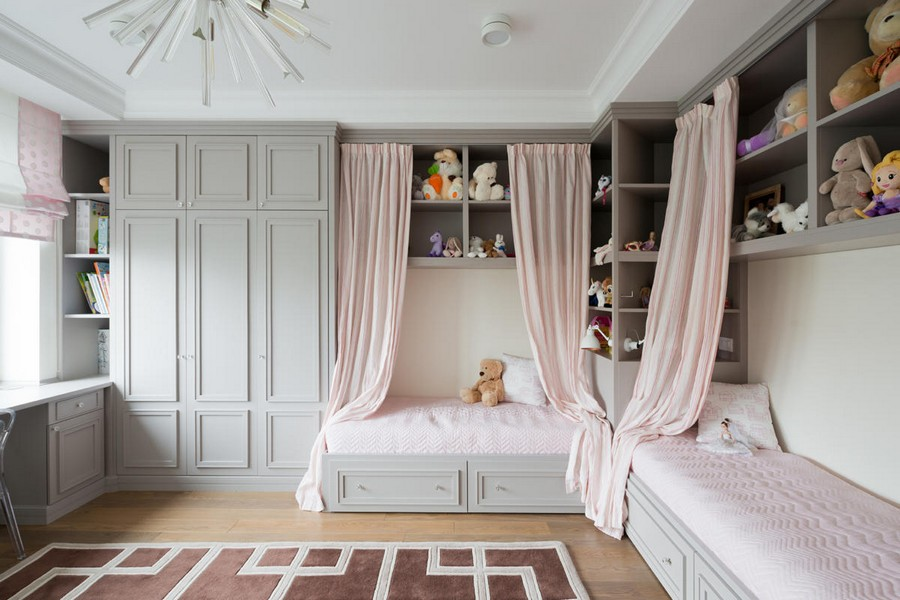 7-American-style-interior-wooden-wall-door-panelling-kids-room-two-beds-with-storage-drawers-powder-pink-and-gray-open-racks-interior-curtains-geometrical-rugs-roman-blinds