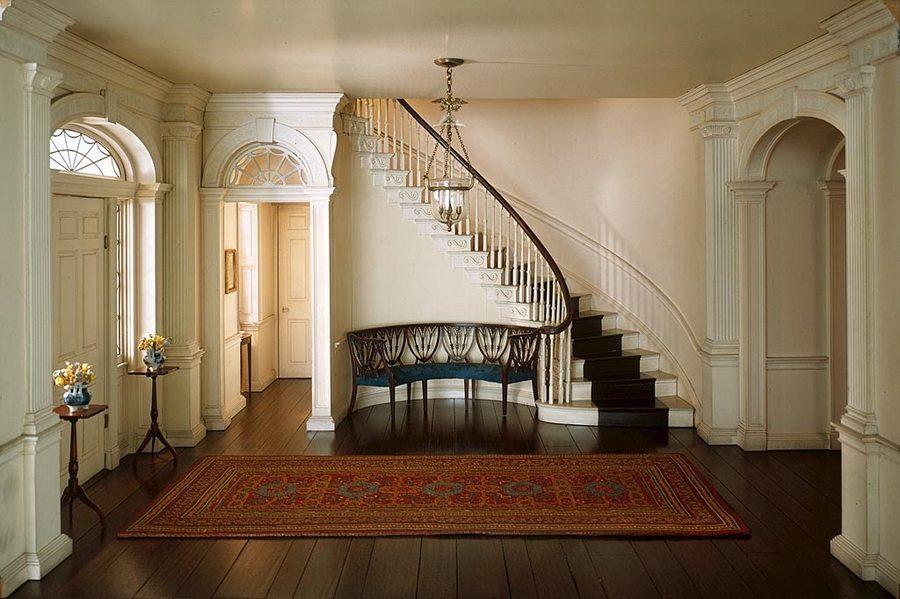 0-hallway-entry-entrance-hall-interior-design-classical-style-parquet-floor-carpet-rug-dark-staircase-circular-bench-arches