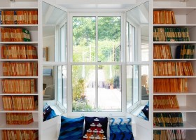 1-1-home-library-interior-design-bookshelves-around-window-aperture-windowsill-bench-reading-spot-corner-by-the-window-mirrored-window-side-jambs-throw-pillows-angled