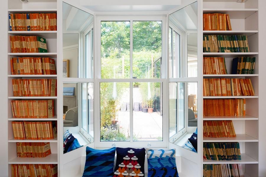 1-1-home-library-interior-design-bookshelves-around-window-aperture-windowsill-bench-reading-spot-corner-by-the-window-mirrored-window-side-jambs-throw-pillows-angled