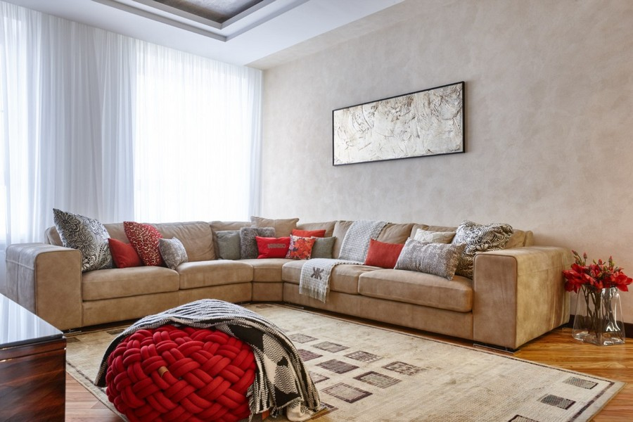 1-4-contemporary-style-interior-design-living-room-light-beige-walls-floor-huge-big-corner-sofa-couch-pillows-rug-red-accents-ottoman-floor-vases-artwork-curtains-stretch-ceiling
