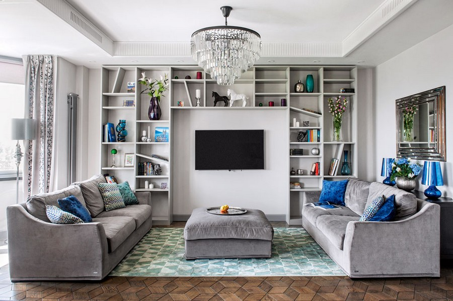 1-art-deco-style-living-room-lounge-interior-design-taupe-gray-monochrome-interior-design-symmetrical-sofas-padded-coffee-table-console-blue-Kartell-lamps-couch-pillows-bookshelves-chandelier-TV-mirror-block
