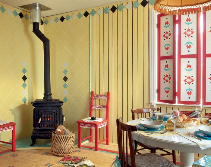 1-country-style-living-dining-room-interior-design-summer-house-yellow-wooden-planks-walls-stove-stenciled-painted-furniture-window-shutters-rustic-ornaments-bright-red-blue-chair-trimming-round-table-floor
