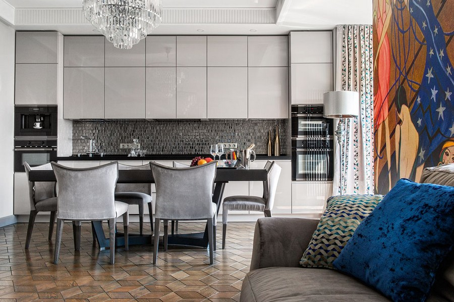 2-open-concept-kitchen-dining-room-in-art-deco-style-monochrome-gray-interior-design-dining-table-chairs-sleek-glossy-cabinets-glass-mosaic-backsplash-tiles-geometrical-mirrored-pattern-chandelier-block-parquet