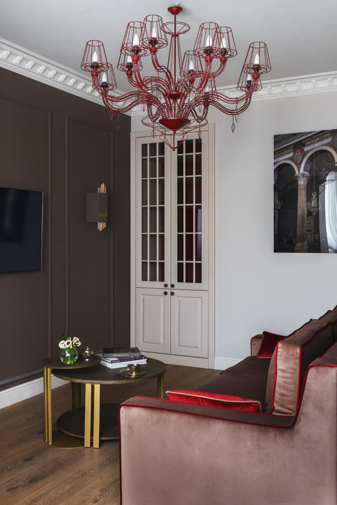 3-chocolate-brown-and-white-living-room-interior-design-light-and-dark-walls-TV-set-round-coffee-table-red-accents-chandelier-sofa-throw-pillows-couch-picture-artwork-doors