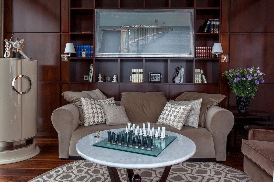 3-classical-style-study-work-room-interior-design-beige-sofa-dark-wood-cabinets-round-rug-coffee-table-chess-bookshelves-seascape-photo-throw-pillows