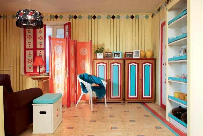 3-country-style-living-room-lounge-interior-design-summer-house-yellow-wooden-planks-walls-room-divider-folding-screen-stenciled-painted-furniture-cabinet-bright-patterns-rustic-ornaments-red-blue-window-shutters