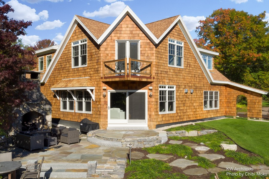 3-traditional-style-house-shingled-roof-cape-cod-house-on-the-Kennebunk-river-bank-American-New-England-patio-outdoor-gas-fireplace-rocks-stone-pathway-garden-path-unusual-angled-wall-circular-porch-roof