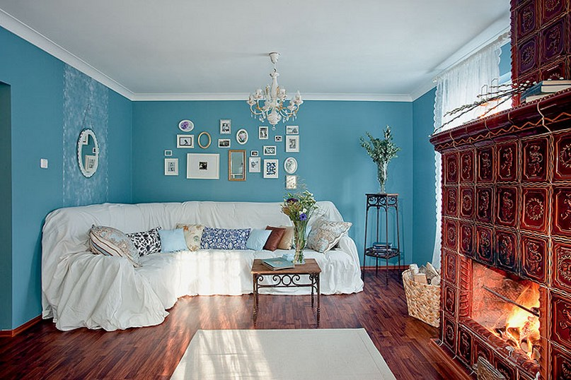 5-beautiful-cozy-country-Scandinavian-style-living-room-in-summer-cottage-blue-walls-brown-glazed-tiles-fireplace-white-corner-sofa-slipcover-wicker-baskets-wrought-metal-whatnot-flower-stand-art-wall-asymmetrical