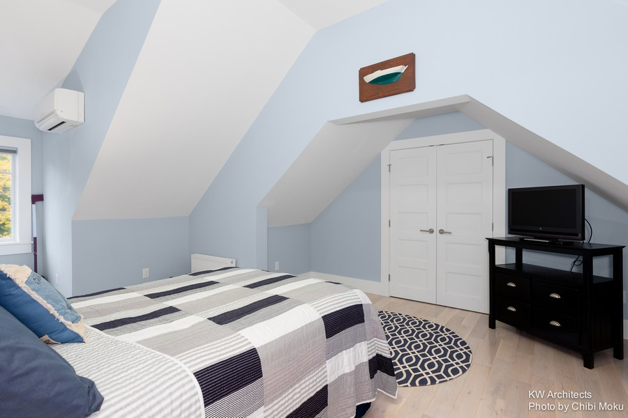 9-contemporary-style-bedroom-interior-design-sloped-ceiling-blue-walls-black-TV-stand-white-door-circular-geometrocal-rug-bed-cover