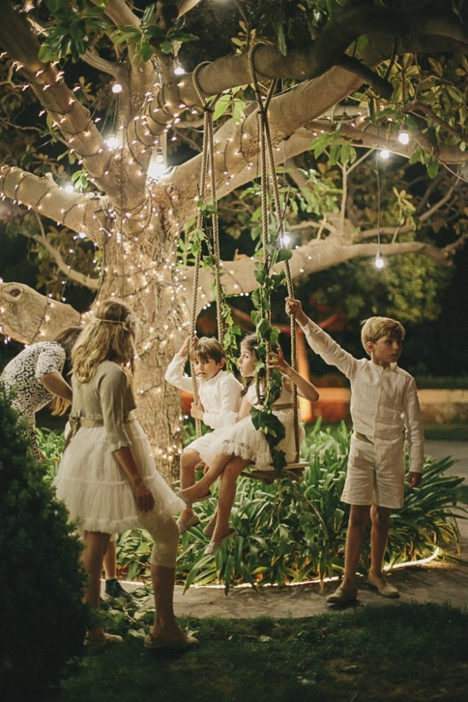 1-2-beautiful-garden-swing-kids-holiday-lights-decorated-tree-children-in-white-party-outdoor-wooden-seat-rope