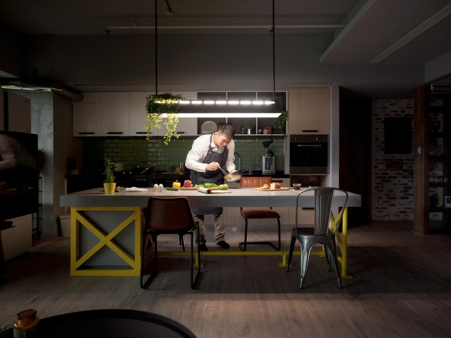 1-3-open-concept-kitchen-interior-design-Taiwan-man-cooking-at-night-island-yellow-table-legs-mismatched-dining-chairs-stools