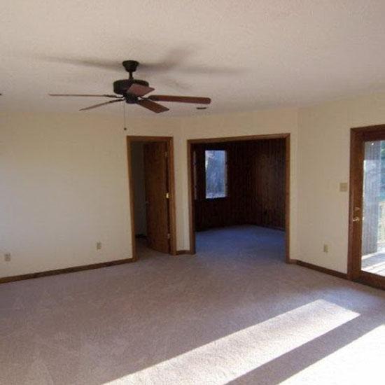 1-empty-bedroom-interior-light-beige-walls-dark-wooden-doors-balcony-exit-with-auxiliary-adjoining-room-ceiling-fan