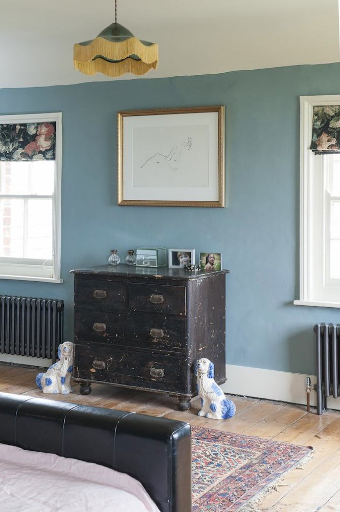 1-old-country-house-interior-design-vintage-style-black-aged-chest-of-drawers-dog-statuettes-carpet-roman-blinds-blue-wall