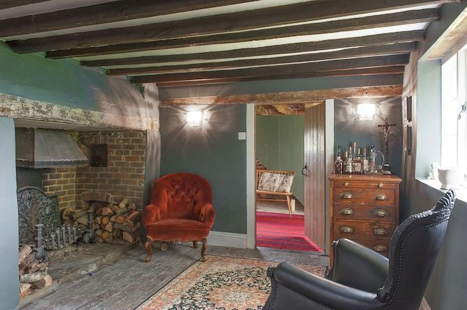 13-old-country-house-interior-design-vintage-style-living-room-English-cottage-chest-of-drawers-wooded-arm-chair-fireplace-aged-floor-crapet-ceiling-beams-low-ceiling
