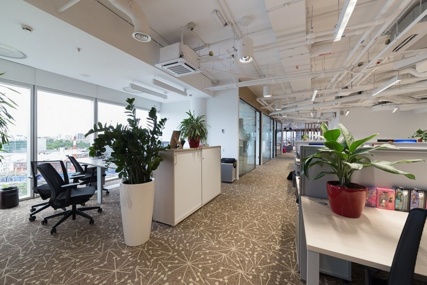 2-1-Mattel-office-interior-design-Russia-Moscow-toys-seller-light-white-walls-exposed-ceiling-pipes-wires-beige-carpeting-panoramic-windows-indoor-plants-white-furniture-desks