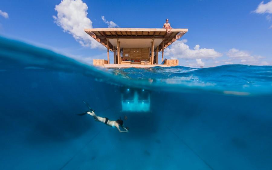 2-Manta-Resort-hotel-Tanzania-Pemba-Island-underwater-under-the-sea-room-woman-diving-under-the-floating-house-sunbathing-roof-terrace