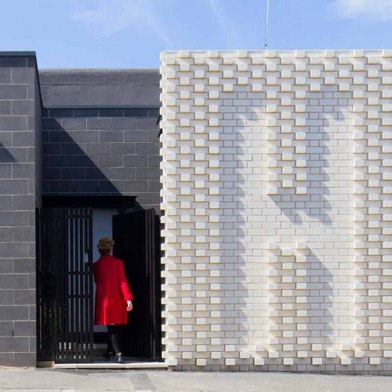 2-creative-small-house-in-Melbourne-suburbs-Australia-white-brick-exterior-wall-with-hello-word-woman-in-red-coat-entering-the-door