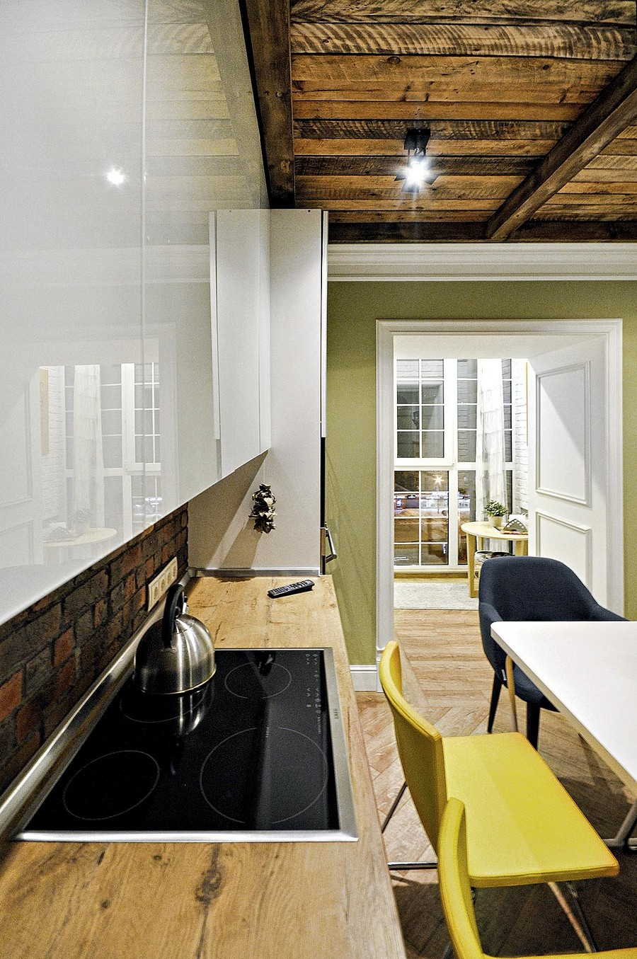 2-kitchen-interior-design-ideas-white-glossy-Scandinavian-style-handleless-cabinets-faux-brick-wall-tiles-backsplash-yellow-gray-dining-chairs-spot-lights-light-parquet-floor-aged-wood-ceiling-balcony-exit