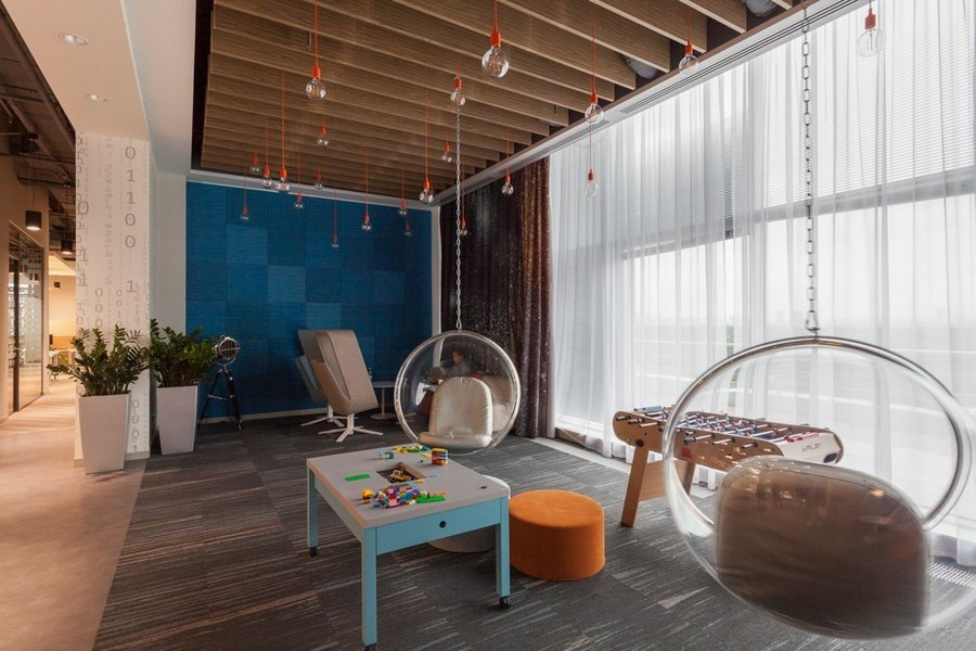 3-1-new-refreshed-renovated-Microsoft-office-headquarters-in-Moscow-interior-design-lounge-zone-rest-white-sheer-curtains-panoramic-windows-floating-ceiling-mounted-transparent-suspended-bubble-chair-blue-wall-red-exposed