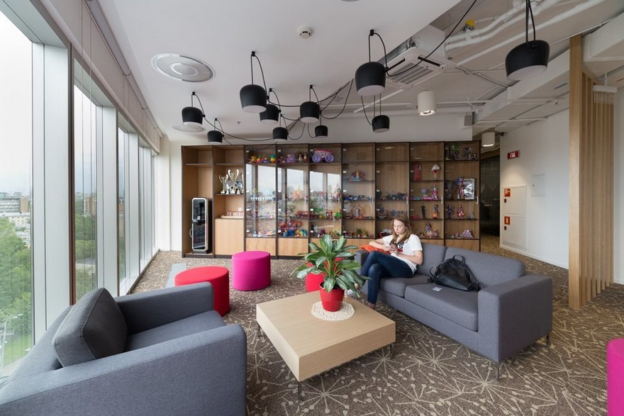 3-Mattel-office-interior-design-Russia-Moscow-toys-seller-light-white-walls-exposed-ceiling-pipes-wires-beige-carpeting-panoramic-windows-indoor-plants-lounge-zone-gray-sofas-bright-pink-ottomans-black-pendant-lamps