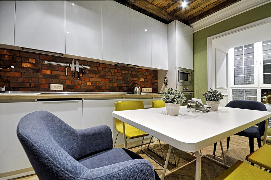3-narrow-kitchen-interior-design-ideas-white-glossy-Scandinavian-style-handleless-cabinets-faux-brick-wall-tiles-backsplash-yellow-gray-dining-chairs-spot-lights-light-parquet-floor-herringbone-pattern