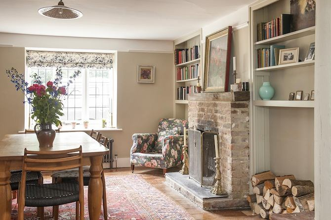3-old-country-house-interior-design-vintage-style-living-dining-room-arm-chair-aged-wooden-floor-firewood-fireplace-bookshelves-table-chairs-flowers-roman-blinds