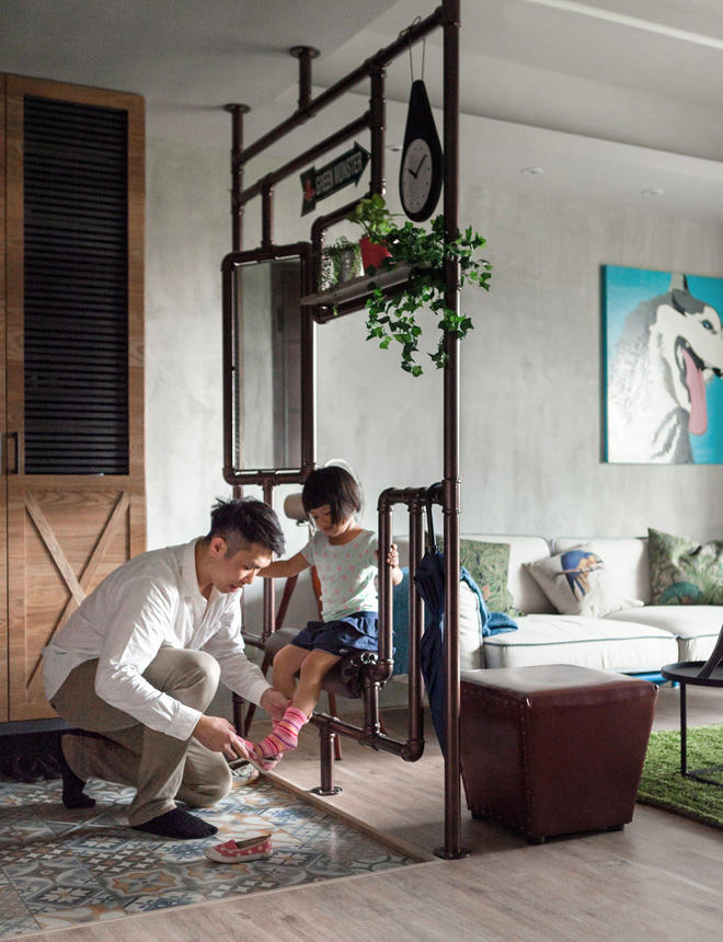 4-1-open-concept-living-room-entry-mudroom-interior-design-Taiwan-father-putting-shoes-on-daughter-metal-pipes-decor-partition-in-loft-style-patchwork-floor-tiles-mirror-bench-plant-stand