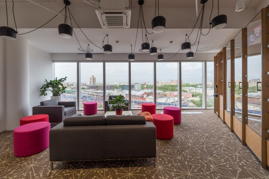 4-2-Mattel-office-interior-design-Russia-Moscow-toys-seller-light-white-walls-exposed-ceiling-pipes-wires-beige-carpeting-panoramic-windows-indoor-plants-lounge-zone-gray-sofas-bright-pink-ottomans-black-pendant-lamps