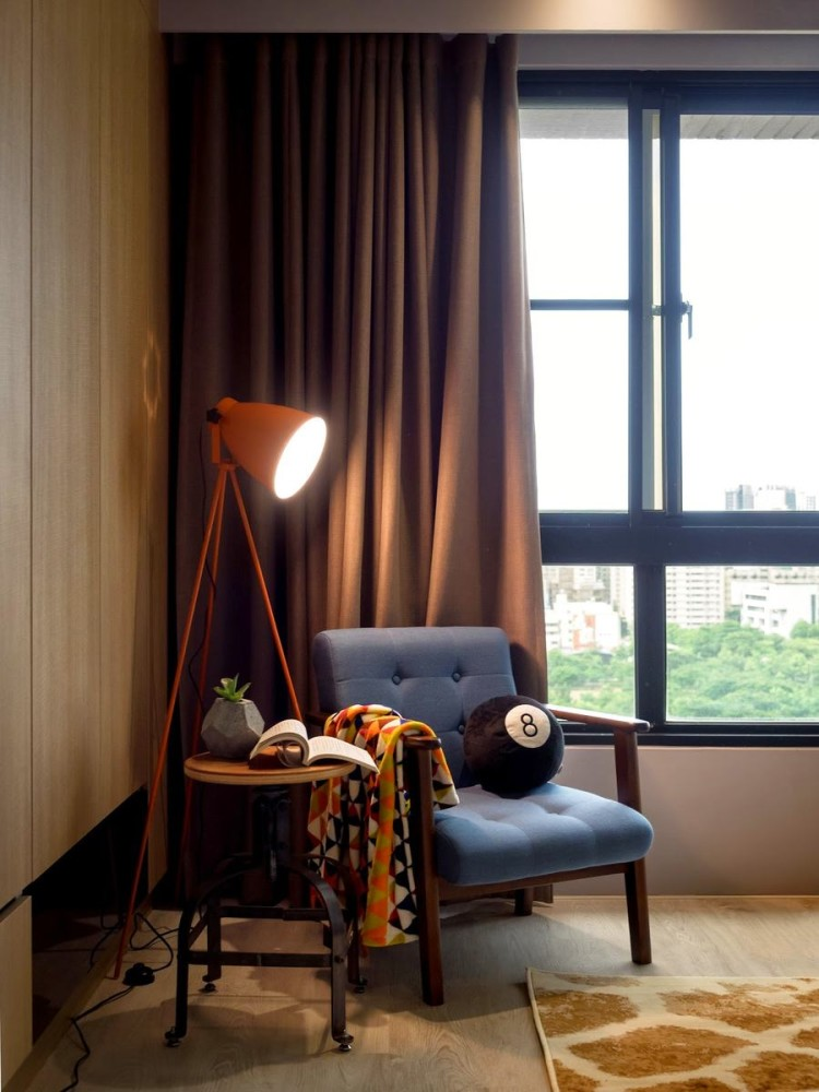 5-2-bedroom-interior-with-panoramic-windows-brown-curtains-rug-blue-arm-chair-floor-lamp-baseball-ball-geometric-flower-pot-coffee-table-blanket