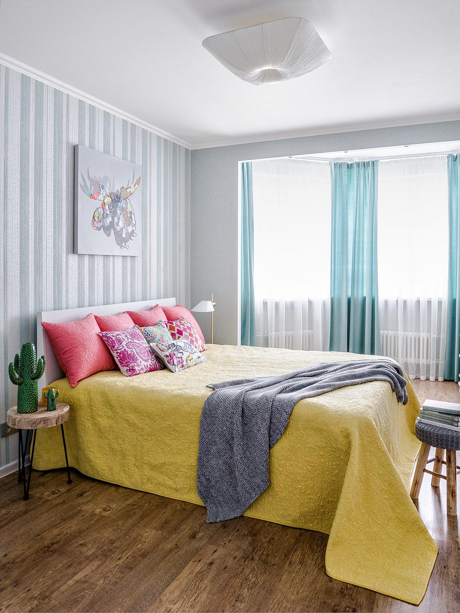 5-contemporary-style-interior-design-airy-light-bright-accents-bedroom-vertical-striped-wallpaper-turquoise-blue-curtains-mustard-yelloe-bed-cover-pink-pillows-cacti-oak-laminate-floor-bay-window