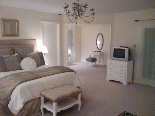 5-neo-classical-style-bedroom-interior-design-light-beige-walls-white-furniture-upholstered-bed-dressing-table-ottoman-chest-of-drawers-rug-oval-mirror-chandelier-TV-set-adjoining-room-doors