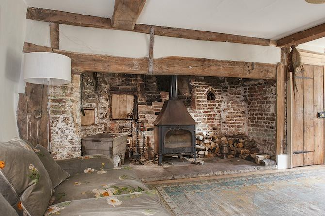 5-old-country-house-interior-design-vintage-style-cottage-living-room-fireplace-stove-brick-masonry-aged-floor-sofa-ceiling-beams-floor-lamp