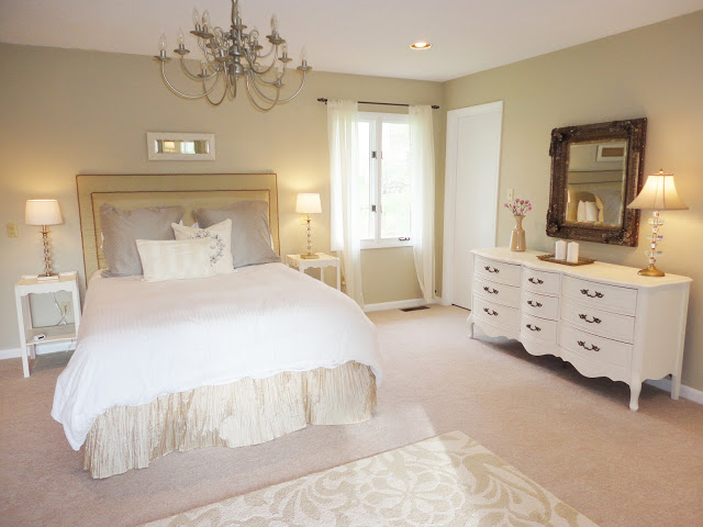 6-1-neo-classical-style-bedroom-interior-design-light-beige-walls-white-furniture-upholstered-bed-bedside-tables-curved-chest-of-drawers-rug-mirror-table-lamps-chandelier